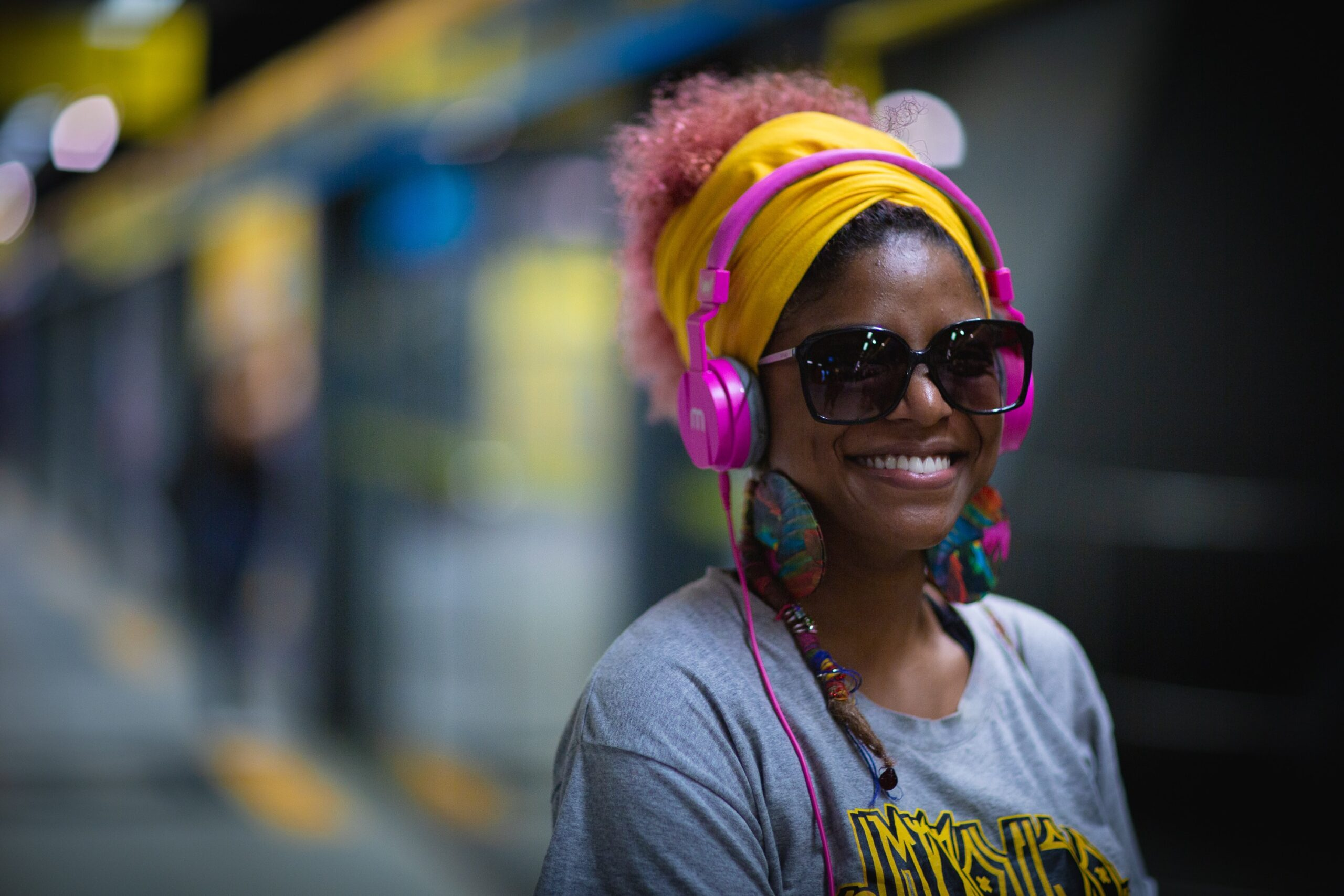 A black woman with pink earphones on a street