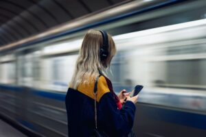A girl with headphones standing on a subway station.